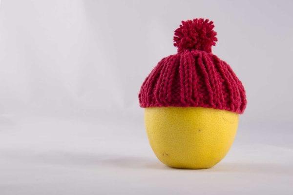 Pompelmo con cappellino lana su sfondo grigio